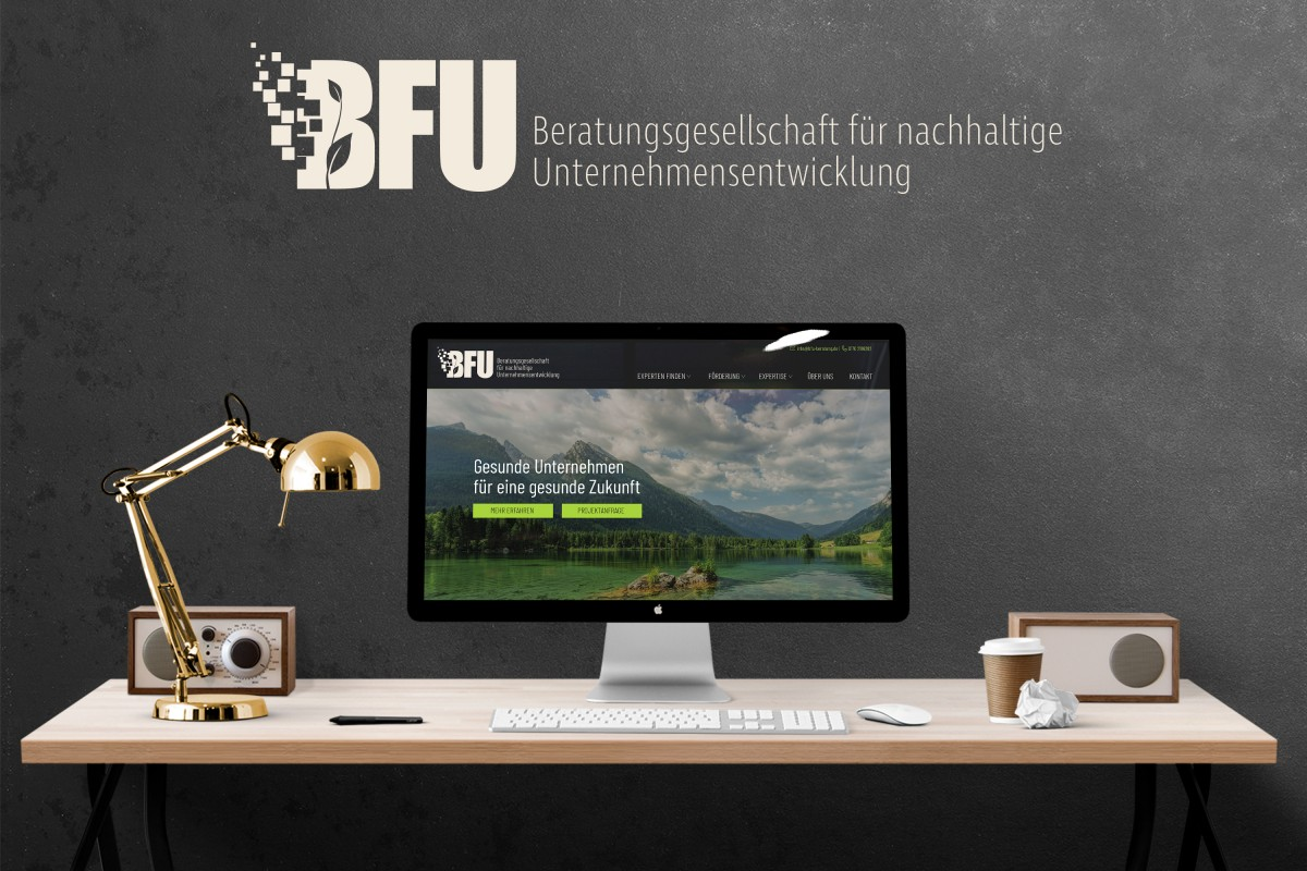 Die Startseite der BFU GmbH auf einem PC-Monitor auf einem Schreibtisch