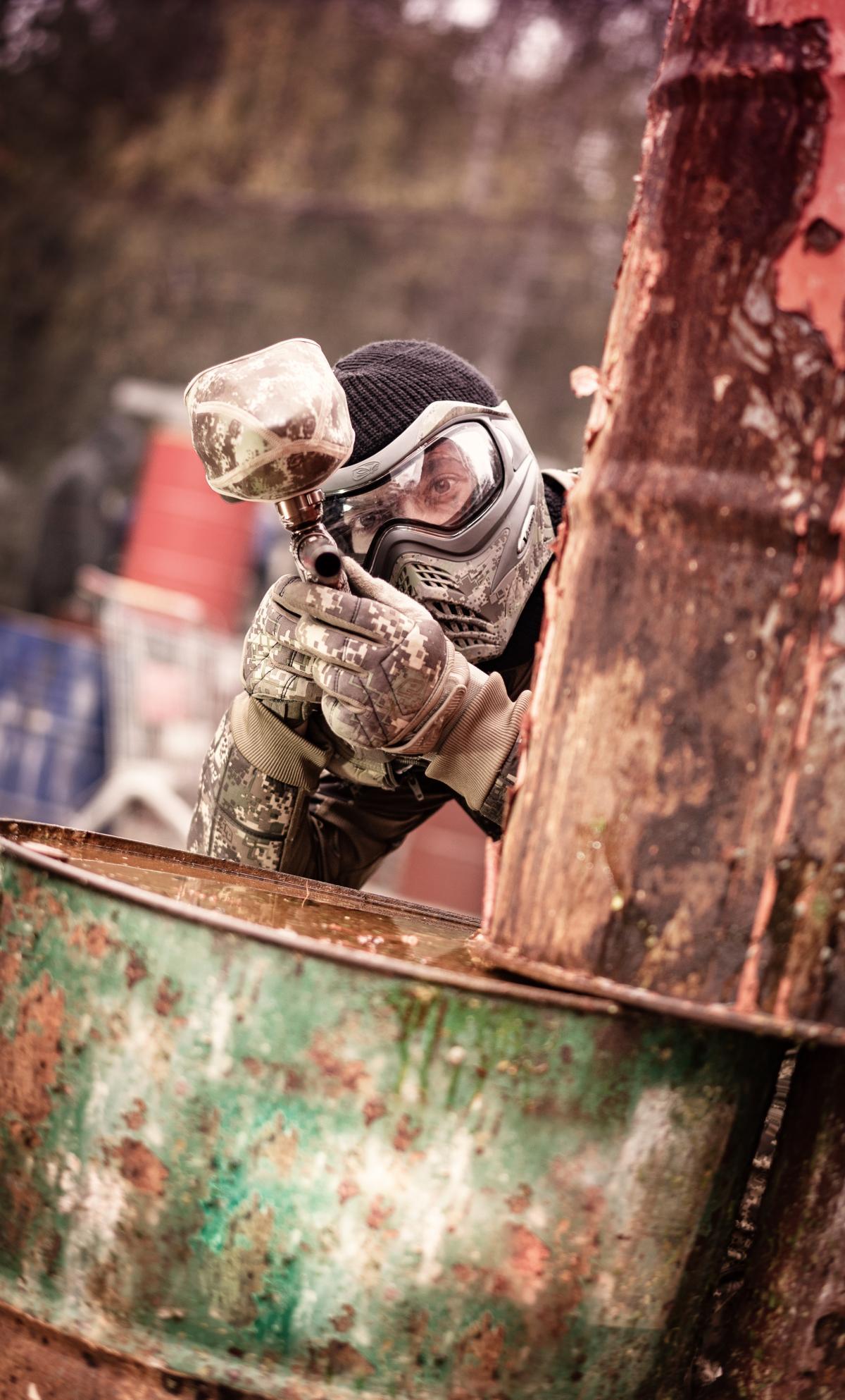 Ein Paintballspieler im Freigelände in Deckung hinter verrosteten Tonnen