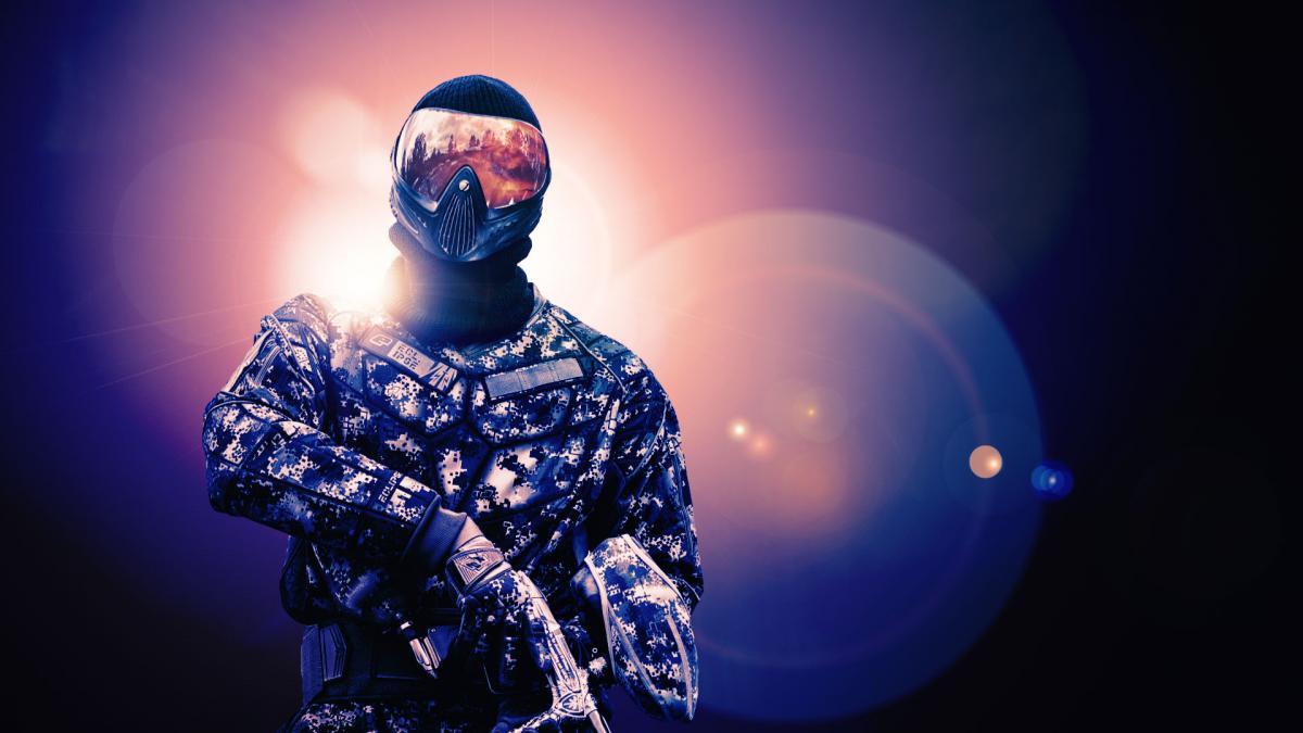 Ein Paintballspieler in der Dunkelheit mit gleißender Lichtquelle im Hintergrund