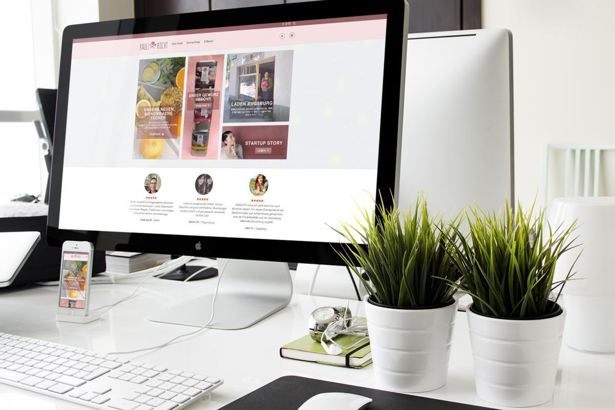 Die Webseite von Paulikocht auf einem PC-Monitor und einem Handy auf einem Schreibtisch
