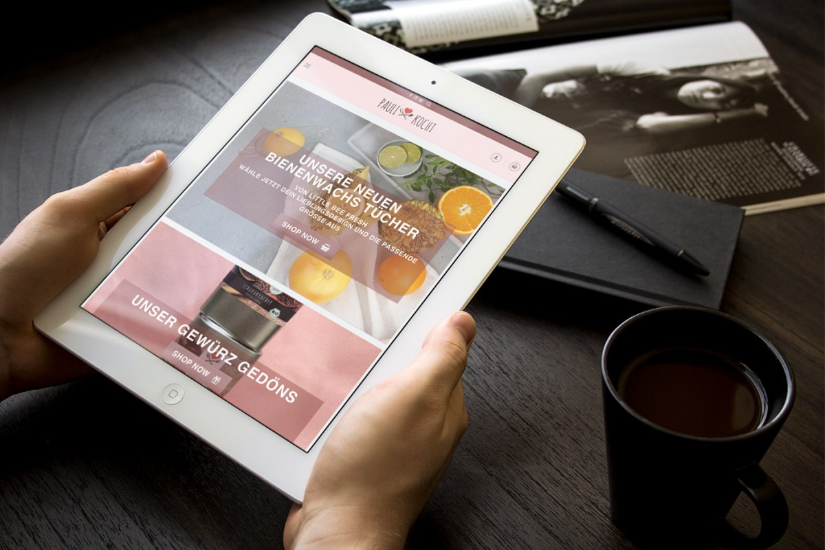 Die Webseite von Paulikocht auf einem Tablet-PC, der vor einem Schreibtisch in Händen gehalten wird
