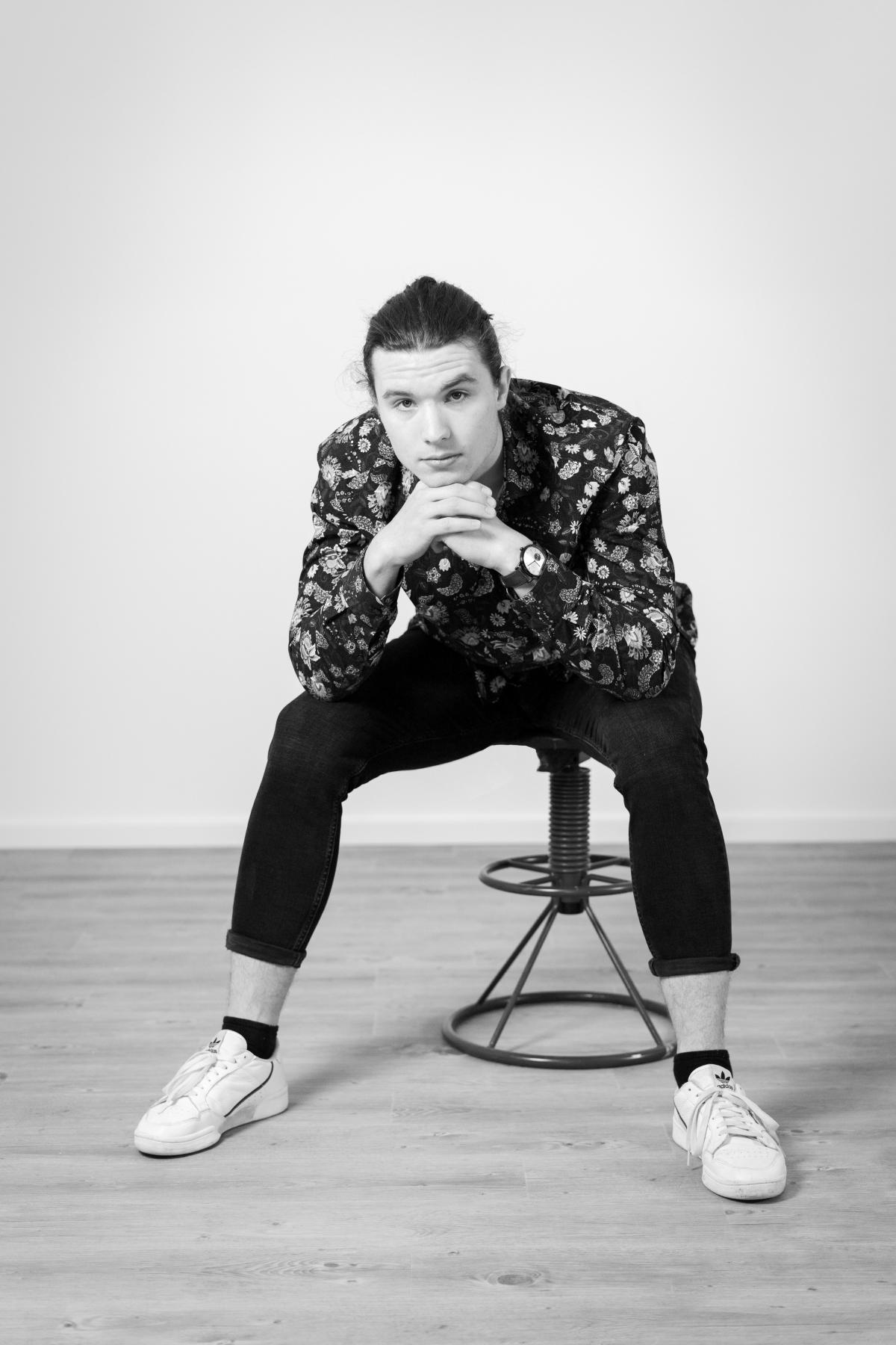 Der Künstler Simon Kohler in nachdenklicher Pose auf einem Hocker